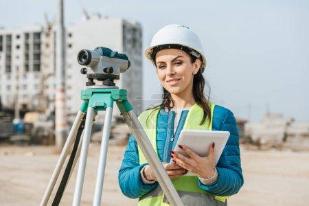 Photo pour Surveyor avec tablette numérique et niveau de mesure souriant à la caméra - image libre de droit