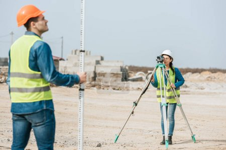 Photo for Selective focus of surveyors using digital level and ruler on construction site - Royalty Free Image