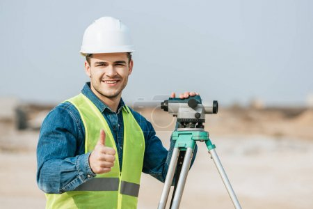 Photo for Smiling surveyor with digital level showing thumb up gesture - Royalty Free Image