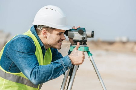 Photo for Smiling surveyor looking through digital level and showing thumb up gesture - Royalty Free Image