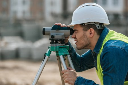 Photo for Side view of surveyor looking through digital level - Royalty Free Image