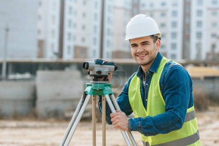 Photo pour Sondeur souriant au niveau numérique regardant la caméra sur le chantier de construction - image libre de droit