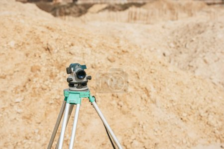 Photo for Digital level on tripod with sand mounds on background - Royalty Free Image