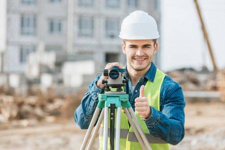 Photo pour Surveyor avec niveau numérique souriant à la caméra et montrant le pouce vers le haut geste - image libre de droit