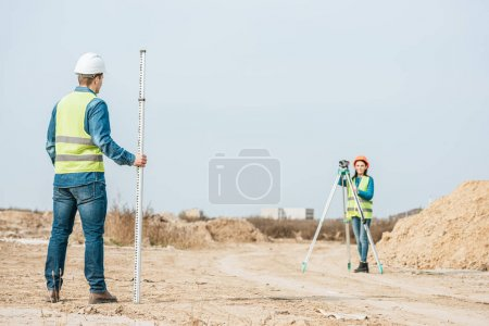 Photo for Surveyors using digital level and survey ruler on dirt road - Royalty Free Image