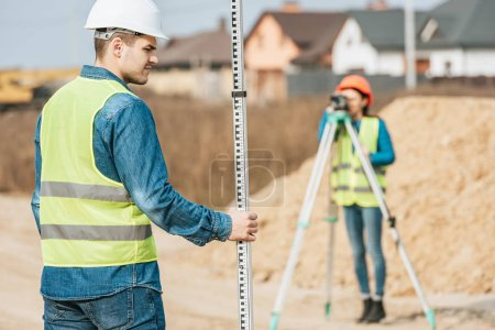 Photo for Selective focus of surveyor with ruler and colleague with digital level on background - Royalty Free Image