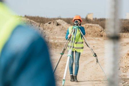 Photo pour Point de mire sélectif de l'arpenteur au niveau numérique et collègue avec règle sur un chemin de terre - image libre de droit