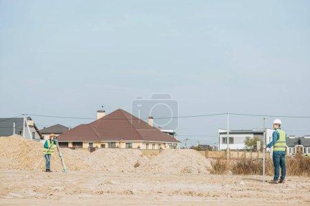 Photo pour Arpenteurs avec règle de niveau numérique travaillant sur un chemin de terre avec monticules de sable - image libre de droit