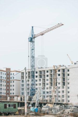 Photo pour Terrain à bâtir avec grues et matériaux de construction - image libre de droit