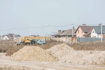 Photo for Sand molds on dirt road with building crane and houses at background - Royalty Free Image