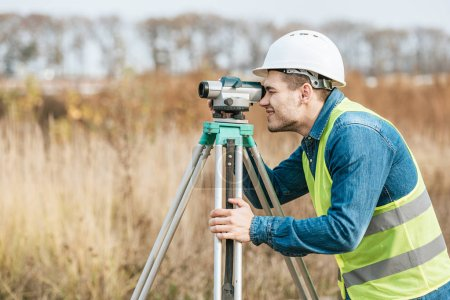 Photo for Side view of surveyor looking through digital level in field - Royalty Free Image
