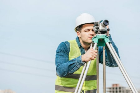 Photo for Surveyor in hardhat and high visibility jacket looking through digital level - Royalty Free Image