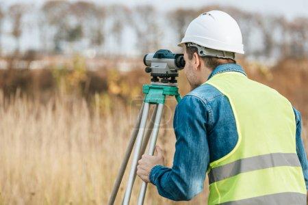 Photo pour Surveyor regardant à travers le niveau numérique dans le domaine - image libre de droit