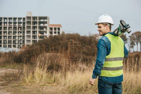 Photo pour Arpenteur au niveau numérique avec terrain et chantier en arrière-plan - image libre de droit