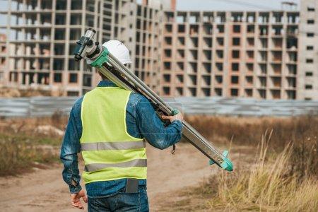 Photo pour Vue arrière de l'arpenteur tenant le niveau numérique avec le chantier en arrière-plan - image libre de droit