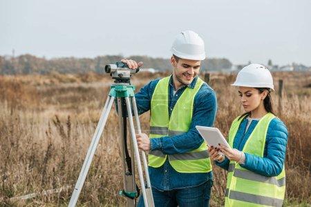 Photo pour Surveyors travaillant avec le niveau numérique et tablette dans le domaine - image libre de droit