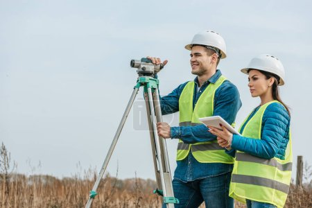 Photo for Surveyors with with digital level and tablet in field - Royalty Free Image