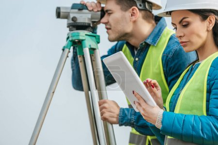 Photo for Selective focus on surveyor with tablet and colleague with digital level - Royalty Free Image