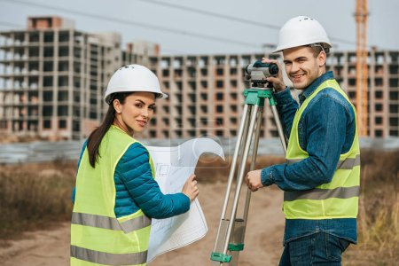 Photo for Smiling surveyors with blueprint and digital level - Royalty Free Image