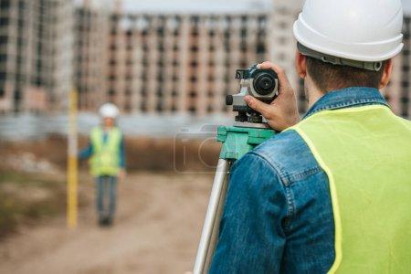 Photo pour Choix sélectif des géomètres qui mesurent les terres au niveau numérique sur le chantier de construction - image libre de droit