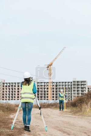 Photo for Surveyors measuring land on dirt road of construction site - Royalty Free Image