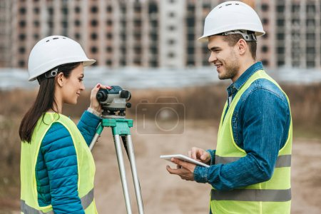 Photo for Smiling surveyors with tablet and digital level - Royalty Free Image
