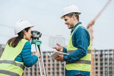 Photo for Surveyors using tablet and digital level on construction site - Royalty Free Image