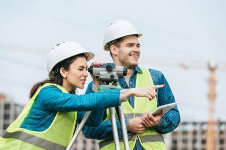 Photo pour Surveyor regardant à travers le niveau numérique et pointant vers un collègue avec tablette - image libre de droit