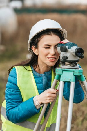 Photo for Attractive smiling surveyor working with digital level - Royalty Free Image