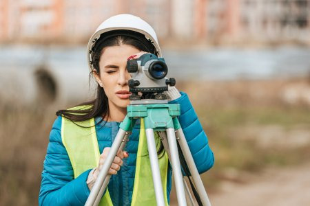 Photo for Attractive surveyor in hardhat working with digital level - Royalty Free Image