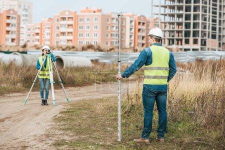 Photo for Surveyors measuring land with digital level and ruler - Royalty Free Image