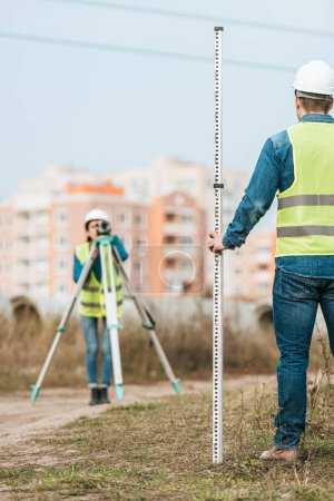 Photo for Selective focus of surveyors measuring land with digital level and ruler - Royalty Free Image