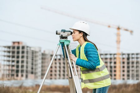 Photo for Side view of Surveyor measuring land with digital level - Royalty Free Image