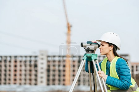 Photo for Side view of Surveyor working with digital level - Royalty Free Image