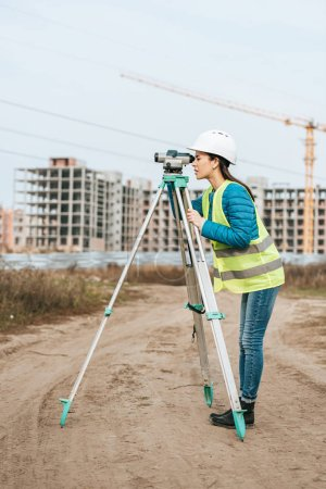 Photo for Surveyor working with digital level on dirt road - Royalty Free Image