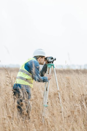 Photo for Surveyor with digital level measuring field - Royalty Free Image