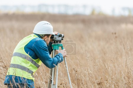 Photo for Surveyor with digital level working in field - Royalty Free Image