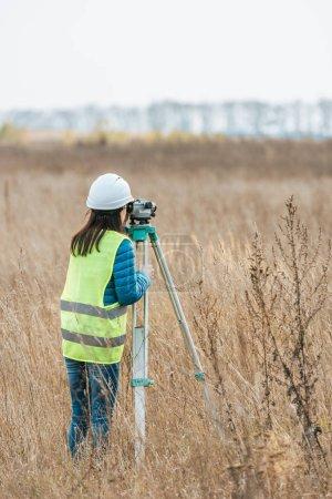 Photo pour Vue arrière de l'arpenteur travaillant au niveau numérique sur le terrain - image libre de droit