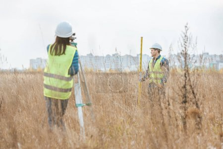 Photo for Surveyors working with digital level and ruler in field - Royalty Free Image
