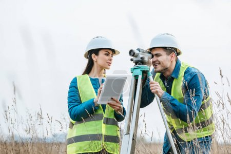 Photo for Surveyors working with digital level and tablet in field - Royalty Free Image