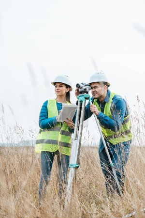 Photo for Surveyors working with digital level and using tablet in field - Royalty Free Image