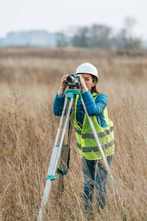 Photo for Female surveyor working with digital level in field - Royalty Free Image