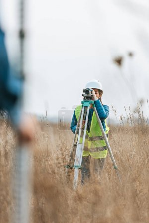 Photo for Selective focus of surveyors measuring land with digital level and ruler in field - Royalty Free Image