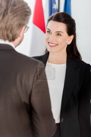 Photo for Selective focus of happy woman looking at diplomat near american flag - Royalty Free Image