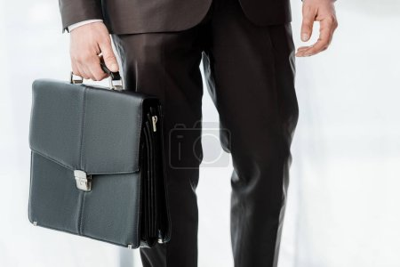 Photo for Cropped view of diplomat standing with leather briefcase - Royalty Free Image