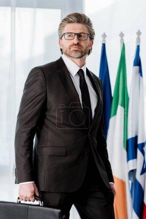 Photo pour Beau diplomate barbu tenant un porte-documents près des drapeaux - image libre de droit
