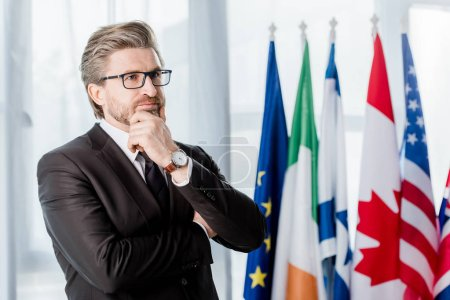 Photo for Pensive diplomat in glasses touching face near flags in embassy - Royalty Free Image