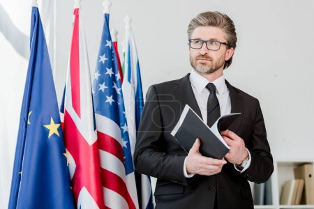 Photo for Bearded diplomat holding folder near flags - Royalty Free Image