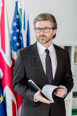 Photo pour Beau diplomate dans des lunettes tenant dossier près des drapeaux du royaume américain et uni - image libre de droit
