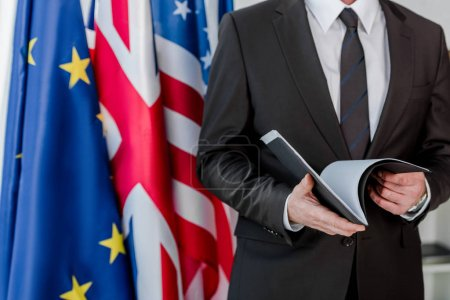 Photo for Cropped view of diplomat holding folder near flags - Royalty Free Image